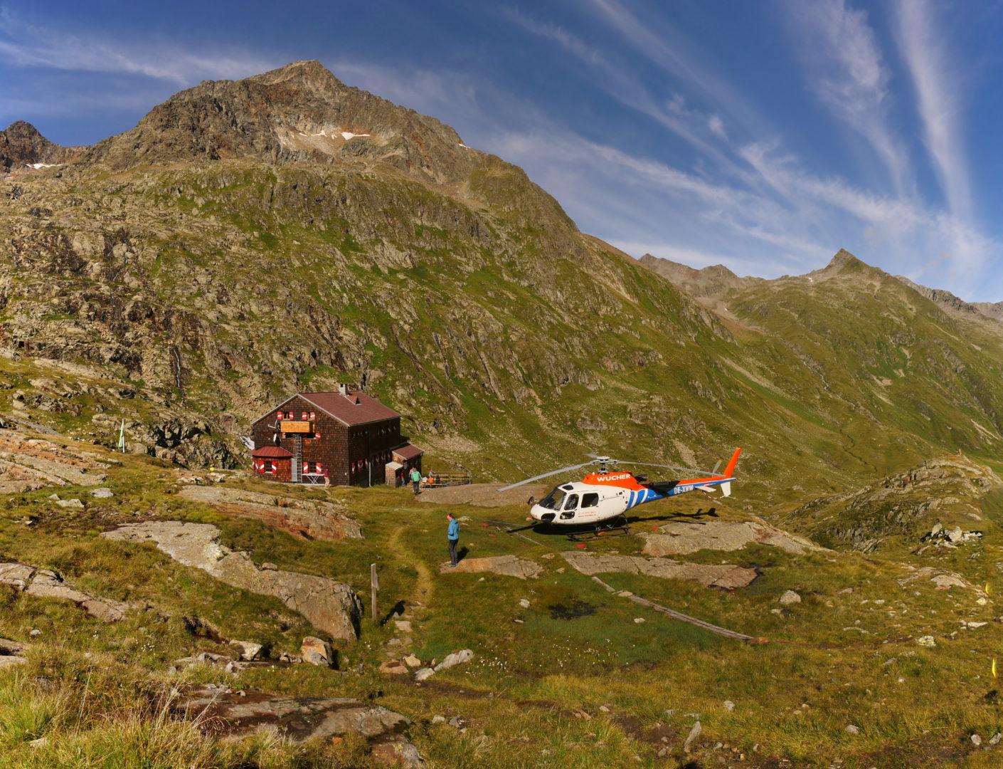 Helikopter vor der Hütte, dahinter Roter Knopf 3296 m)